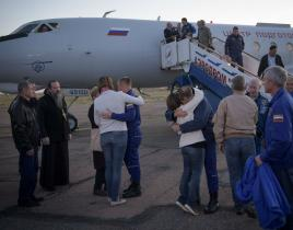 Nasa Flight Engineer Alexey Ovchinin of Roscosmos and Flight Engineer Nick Hague of NASA embrace their families after landing at the Krayniy Airport in Baikonur, Kazakhstan